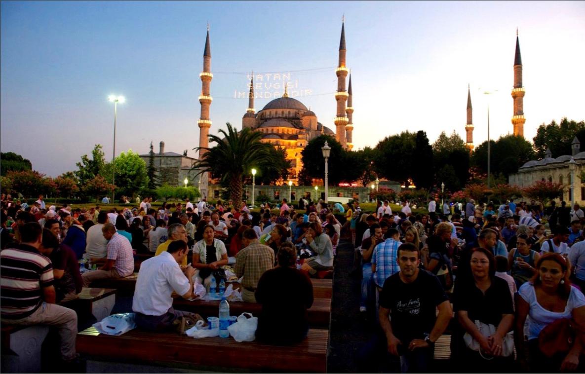 kuvituskuva, ihmisiä ulkona istumassa iltaa moskeija taustalla