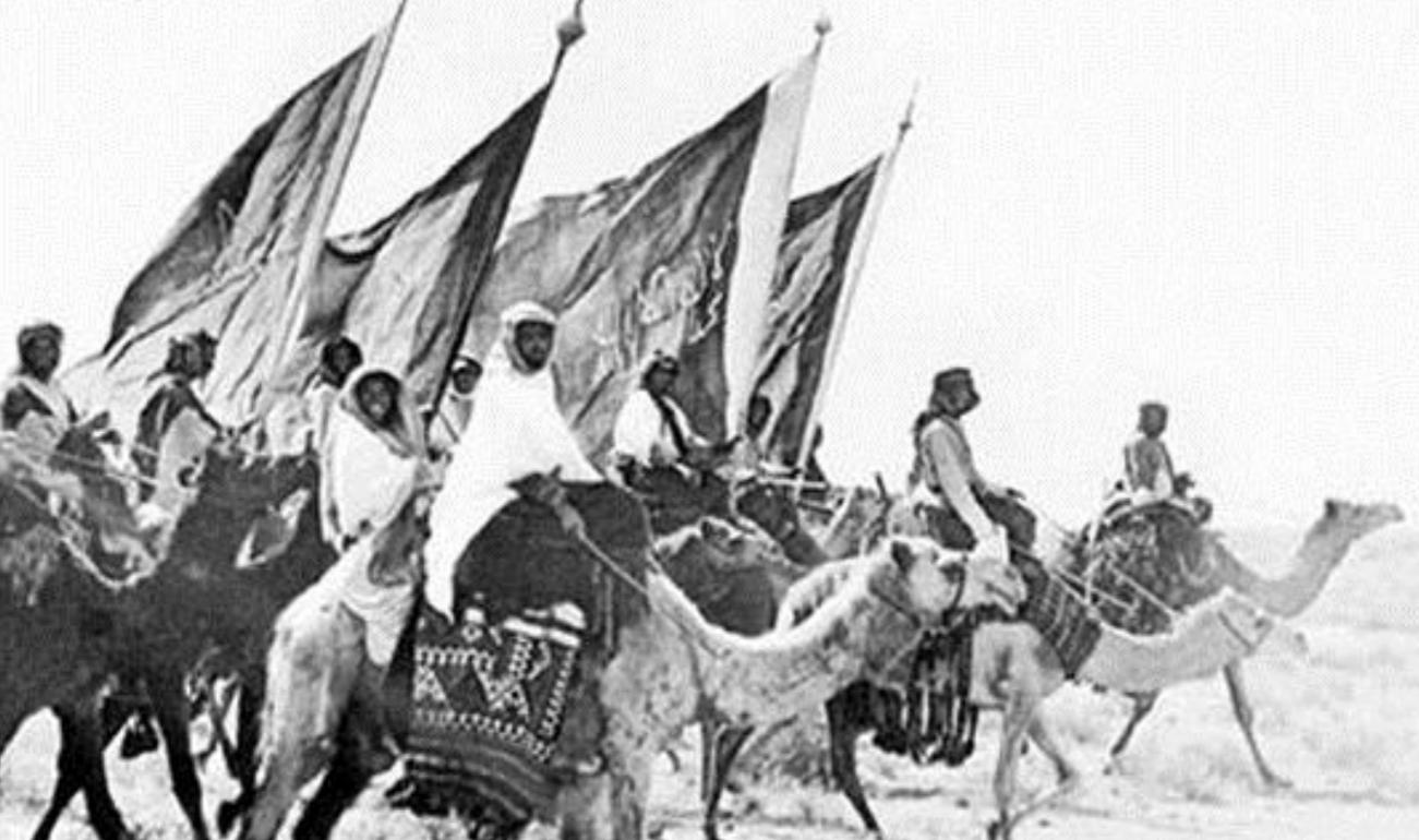 mustavalkoinen kuvituskuva, ihmisiä kamelien selässä lippujen kanssa