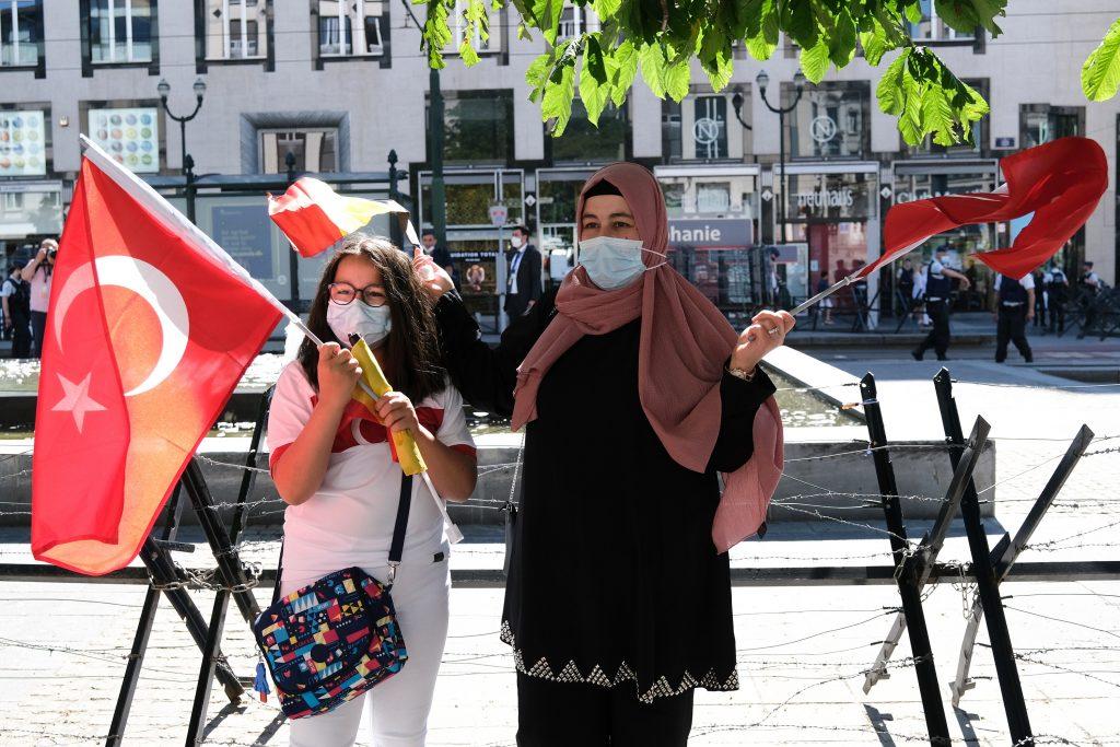 Kaksi naista seisoo Turkin lippujen kanssa aukiolla Bryselissä.