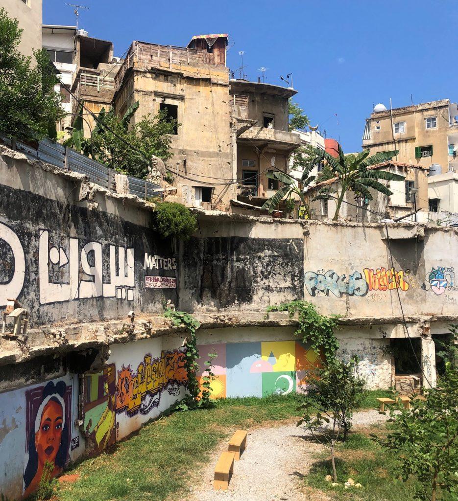 Kuvassa vanhoja kerrostaloja, joiden edustalla on puisto ja graffititaidetta.