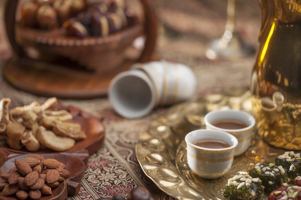 Kultaisella tarjottimella on kaksi pientä kuppia kahvia sekä arabialaisia herkkuja. Koristeellisen pöytäliinan päällä on kaksi puista lautasta, joille on aseteltu manteleita ja taateleita.