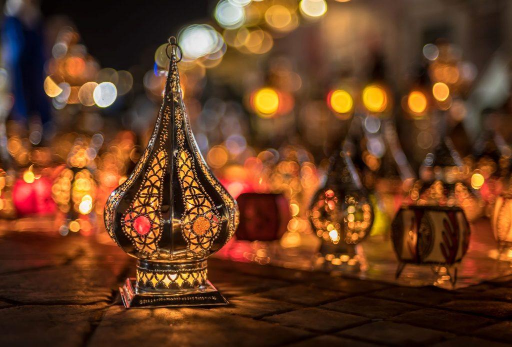 Joukko koristeellisia kynttilälyhtyjä loistaa kadulle aseteltuna pimeässä.