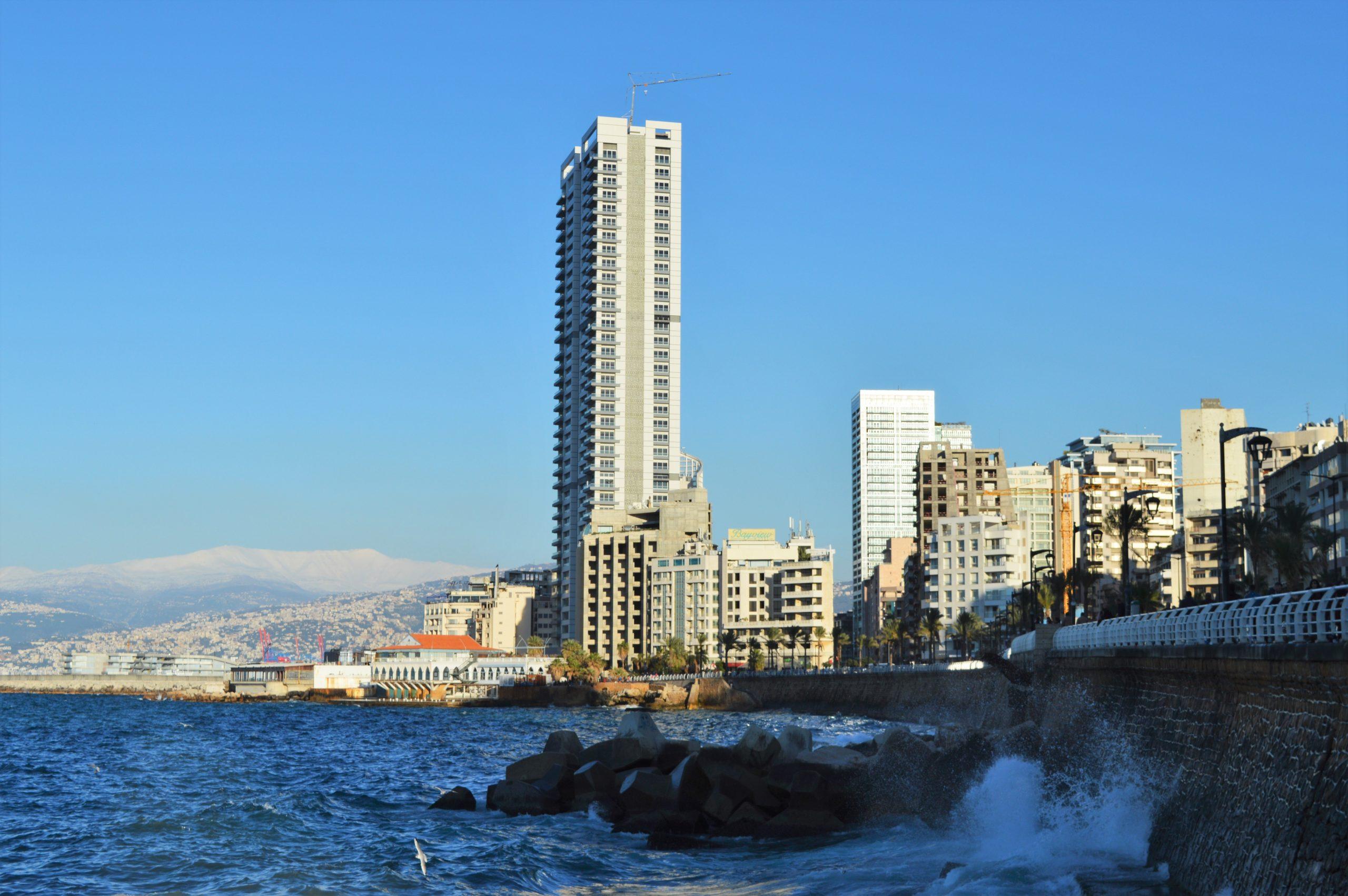 Beirutin rantabulevardi, jossa näkyy korkeita rakennuksia taustalla, ja aallot edustalla.